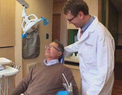 Dentist smiling at dental patient in exam chair