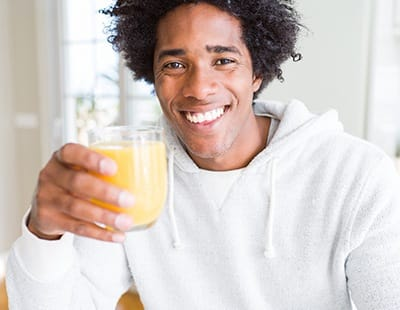 person smiling and drinking a glass of juice