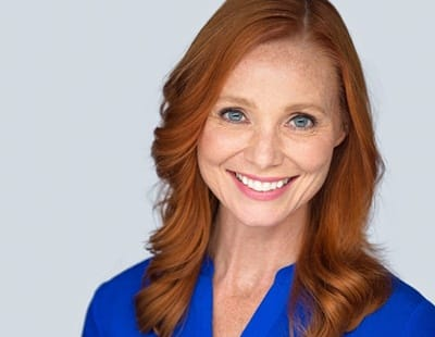 A middle-aged woman with red hair smiling after fully recovering from dental implant placement