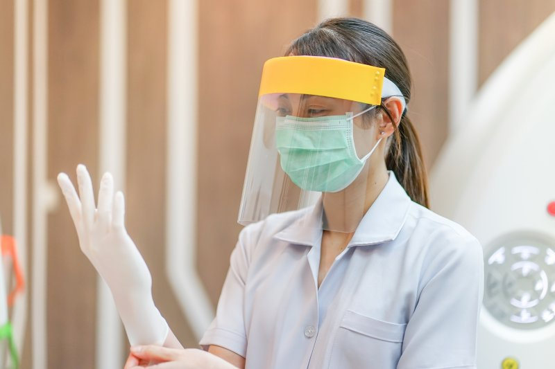 Dentist in Frederick putting on PPE